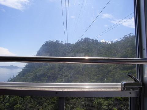 榧谷(かやたに)駅で乗り換え、獅子岩(ししいわ)駅(終点)まで交走式ロープウェー  に乗った。距離0.52km、約5分、高さ525m。  交走式ロープウェーは、2台の客車が山頂と山麓を交互に往復するシステムで、大きな搬器を用いて一度に多くの乗客を運ぶことが出来る。高速運転も可能で、長い距離を短い時間で結びたい場合にも適している。